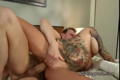 Tattooed brunette gives a sloppy blowjob and takes it to the face in the bed.